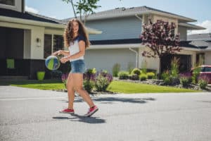 Girl playing basketball on street, Wilden Kelowna
