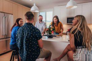 Family around kitchen isle in Wilden townhome image