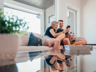 Teenagers on phone sitting on couch in Wilden Townhome image